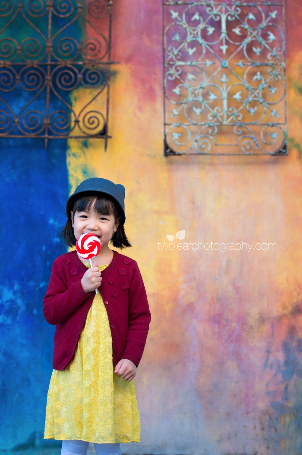 little-girl-licking-lolipop-colorful-wall